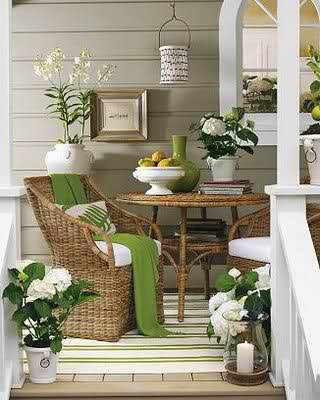 Wicker front porch furniture and delicate green accents make this front porch a relaxing hide-away