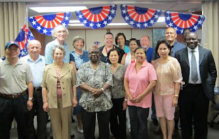 A small section of the Citizenship Preparation Program, including instructors, advocates, and newly naturalized citizens pose for a photo with Program Director Nancy Newton.