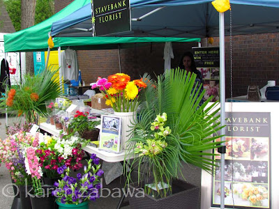 Colourful pots and vases of cut flowers and tropical plants surround Stavebank Florist stall.
