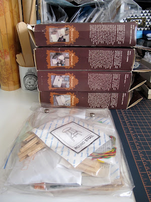 Pile of modern dolls' house miniature upholstery kits on a worktable, next to a bag with more kits in it.