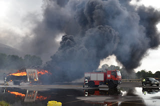 Los bomberos trabajan en las tareas de extinción del incendio de uun camión en la A66