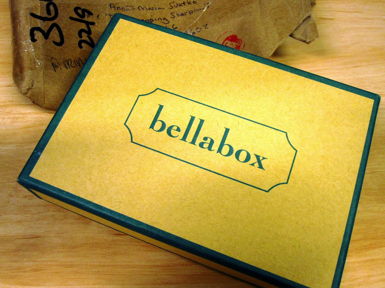 Small cardboard box labeled 'bellabox' on top of postal wrapping.