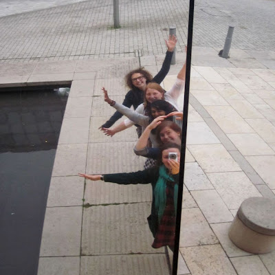 5 girls reflected in a large mirror
