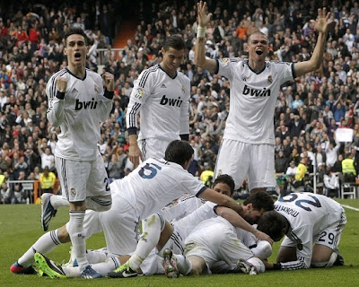 Real Madrid players on the field celebrating the goal against Barcelona