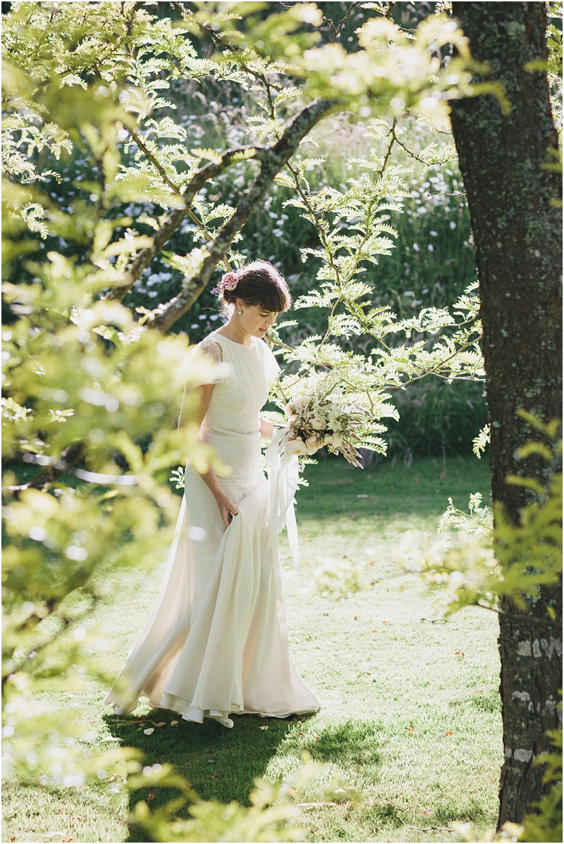Bride walking through sunlit leaves in Belle and Bunty dress