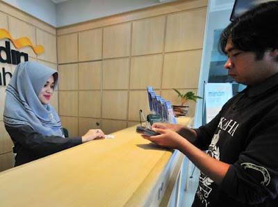 TRANSAKSI : Seorang Teller di Bank Mandiri Syariah Cabang Pontianak tengah melayani nasabah.  FOTO HARYADI/PONTIANAKPOST