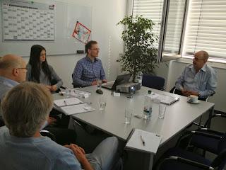 Das Bild zeigt den Konferenzraum, in dem die Schulung für Zeta Producer abgehalten wird. Am Tisch sitzen der Dozent, welcher die Schulung leitet, sowie die übrigen Kursteilnehmer
