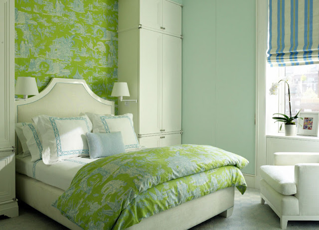 bedroom with wall covered in green toile wallpaper. The bed has a molded headboard and is surrounded by two wall sized wardobes