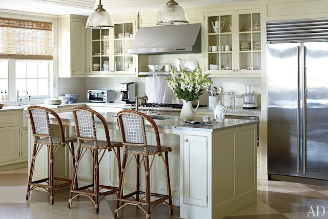 kitchen in Nantucket with stainless appliances, island with marble counter top and high chairs, two pendant lights, white cabinets and subway tile backsplash