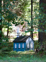 A smal blue-painted wood church at the edge of Marigold Springs; this is a miniature building