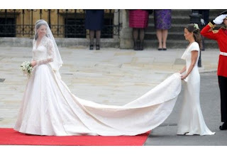 Kate Middleton in her wedding dress with her sister Pippa Middleton holding the train.