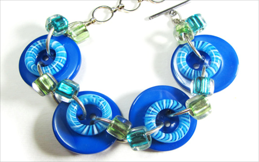 Bold bracelet has big blue buttons, donut beads and square accent beads