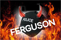 Photo of a police cap that says Police, with devils horns sticking out of the cap with Ferguson written in Capital letters across the police cap and in the background is fire which both depicts hell fire as if the deeds of the police is straight from hell itself and the fire also depicts the riots