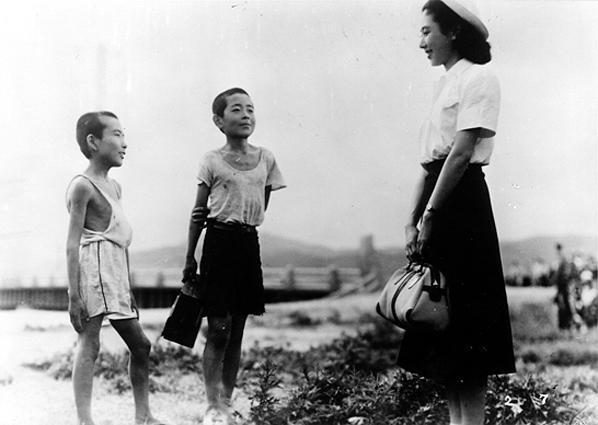 Fotograma del comienzo de la película: Children of Hirosima que muestra a dos niños junto a su maestra. Al fondo Hiroshima devastada.