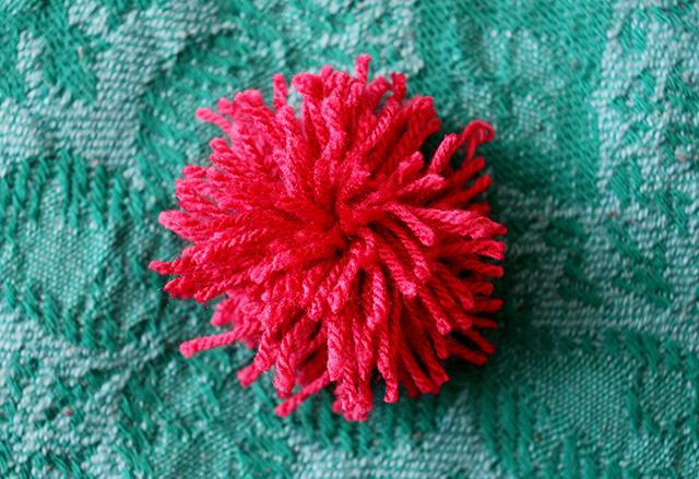 pink handmade pom pom on turquoise blanket