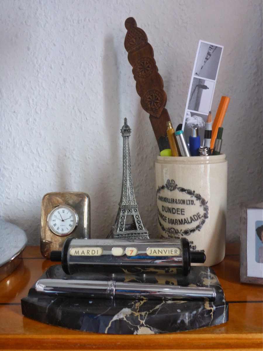 Auf dem Sekretär: Uhr, Stiftköcher, Eiffelturmminiatur, ewiger Kalender.