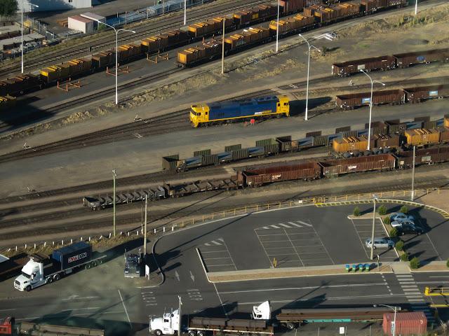 blue locomotive in railyards