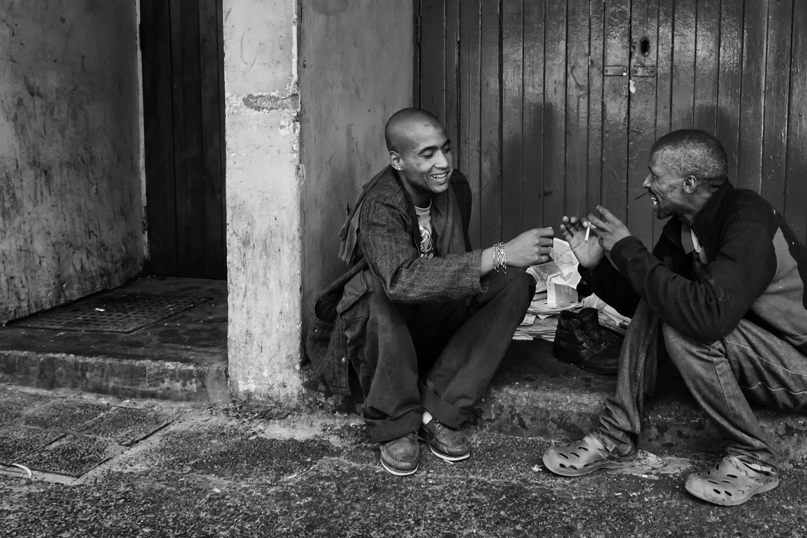 Two men sit on a doorstep in this Cape Town street photograph