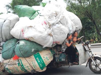 Sebuah keluarga berkongsi kenderaan bersama timbunan sampah di Taiyuan.