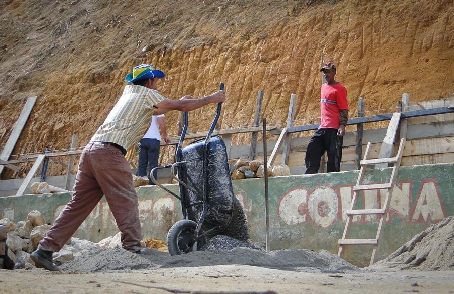 Funcionários da Secretaria de Obras e Serviços Públicos dão continuidade às obras; ao fundo, construção do muro de contenção