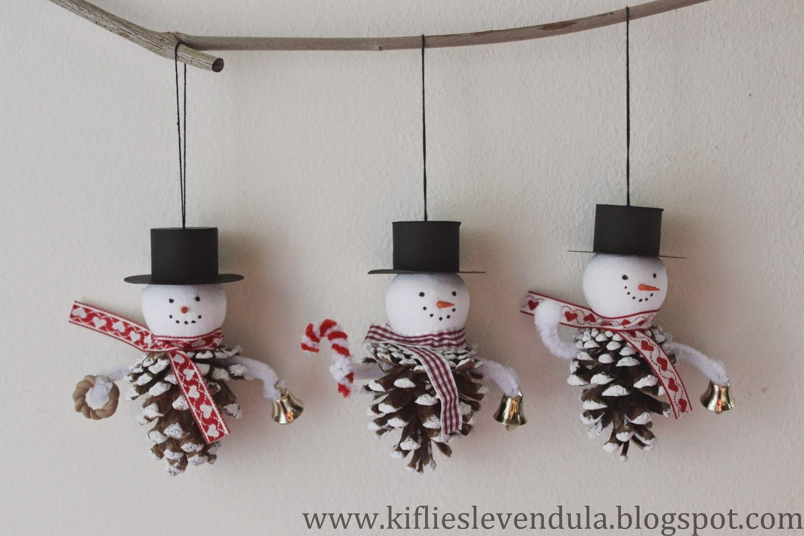 Tres muñecos de nieve creados con piñas y colgados de una ramita