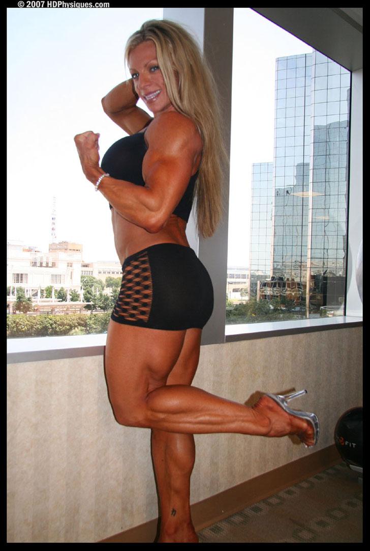 Debi Laszewski Flexing A Bicep And Calf In A Tiny Black Skirt