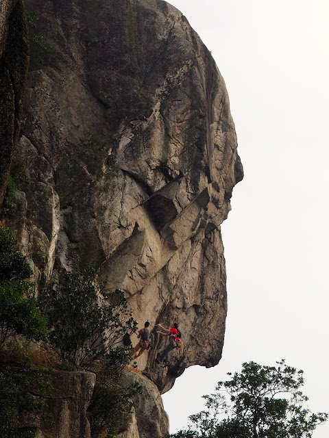 Lion's head rock formation of Lion Rock, with rock climbers on the face, in New Territories, Hong Kong