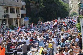 http://1.bp.blogspot.com/-GHinwUXbgU8/UfKsqa2ILbI/AAAAAAAAeK8/h_kxH24zdI0/s640/Perarakan+menentang+rampasan+kuasa+sedang+berlangsung+di+Al-Duqqi+sekarang..jpg