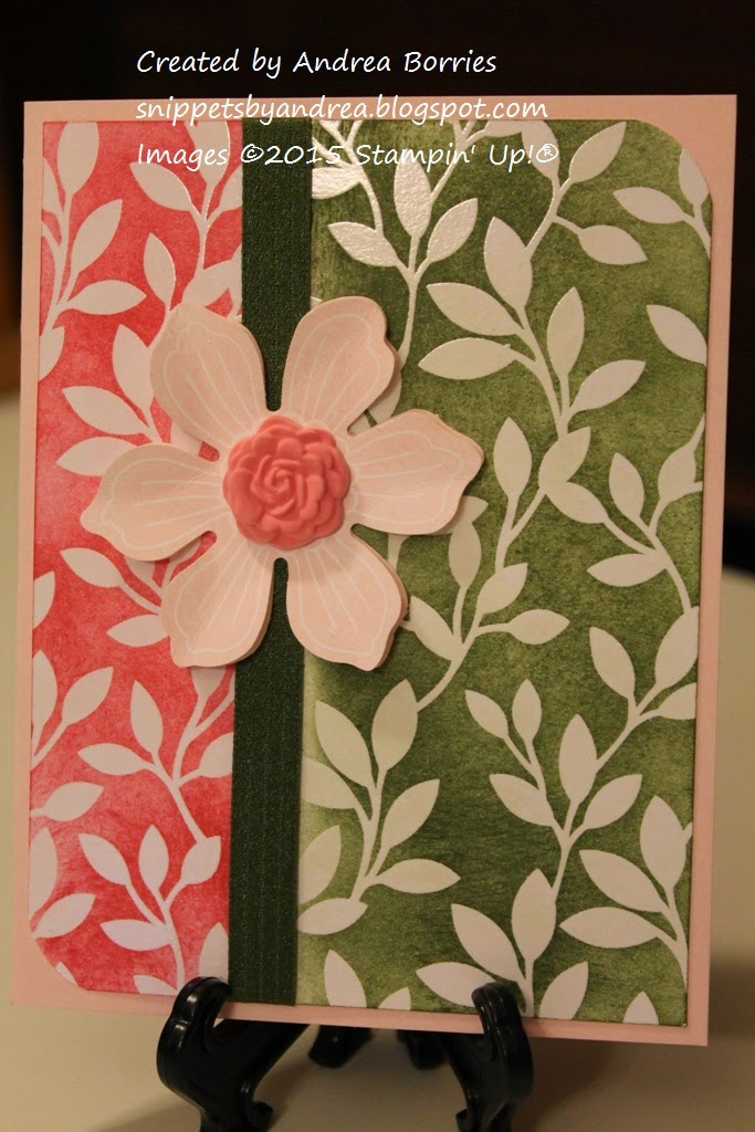 Card with light pink base and a background of leaf-print paper sponged with pink and green ink. A green ribbon is wrapped around the card, and a pink punched flower is the focal point.