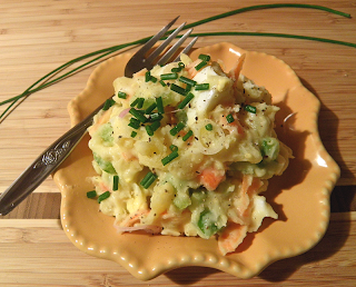 Plate of Potato Salad with Chives in Background