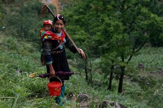 Mujer jóven con su pequeño yendo a arar el arrozal.
