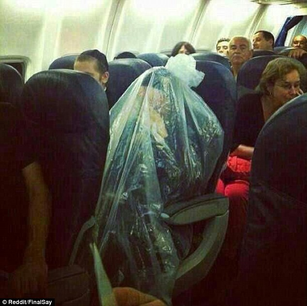 A photograph of an Ultra Orthodox Jewish man wrapped in a life-size plastic bag after boarding a plane
