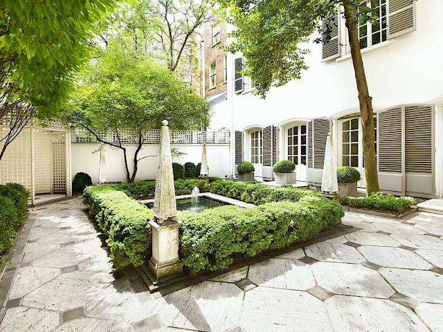 Exterior of a NYC townhouse with grey shutters and a manicured garden