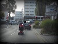 Dame auf elektronischen Rollstuhl auf Strasse