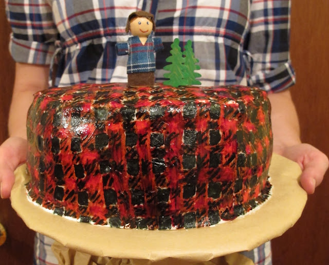 This plaid lumberjack cake was made with fondant and food coloring. A tiny lumberjack made from wood and scrap fabric along with two wooden trees sat atop the cake. I covered an ordinary cake stand in brown butcher paper to make it look like a tree stump.