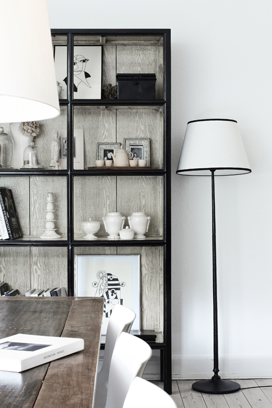 Impressive black glass cabinetry with rough wood interiors via Elle Decoration