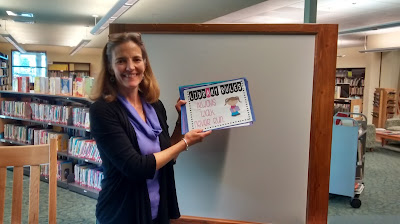 Beige-skinned woman with shoulder-length brown hair stands in front of a whiteboard in a wooden frame. She holds up a stack of posters with cartoon-style illustrations. The one on top reads, 'LIBRARY RULES: Always Walk, Never Run.' Behind her, books are arranged on library shelves