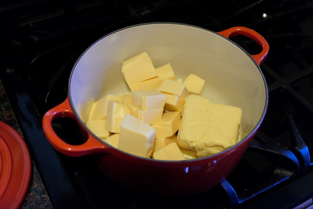 The processed cheese being added into a sauce pot on the stove.