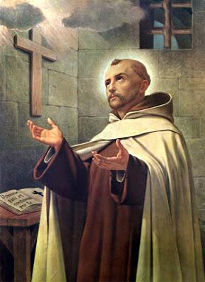 San Juan de la Cruz en una celda con los brazos abiertos recibiendo la Luz Divina