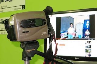 Foto da filmadora em frente ao monitor do computador que passa o vídeo no Youtube