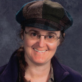 Head and shoulders shot of Cynthia M. Parkhill wearing a brown-and-green paneled 'newsboy' cap