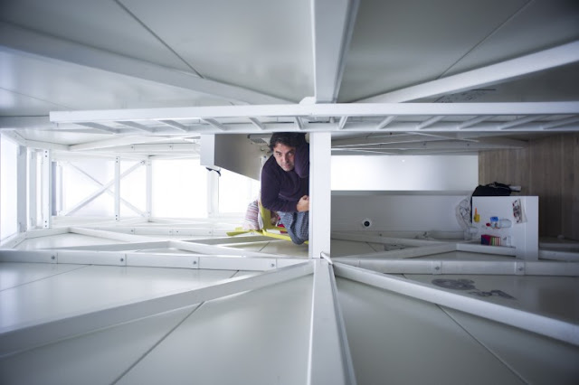 Picture of Keret in his narrow house as seen from the ceiling