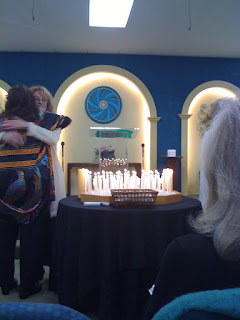 Church group lighting candels, Minister huging a women.