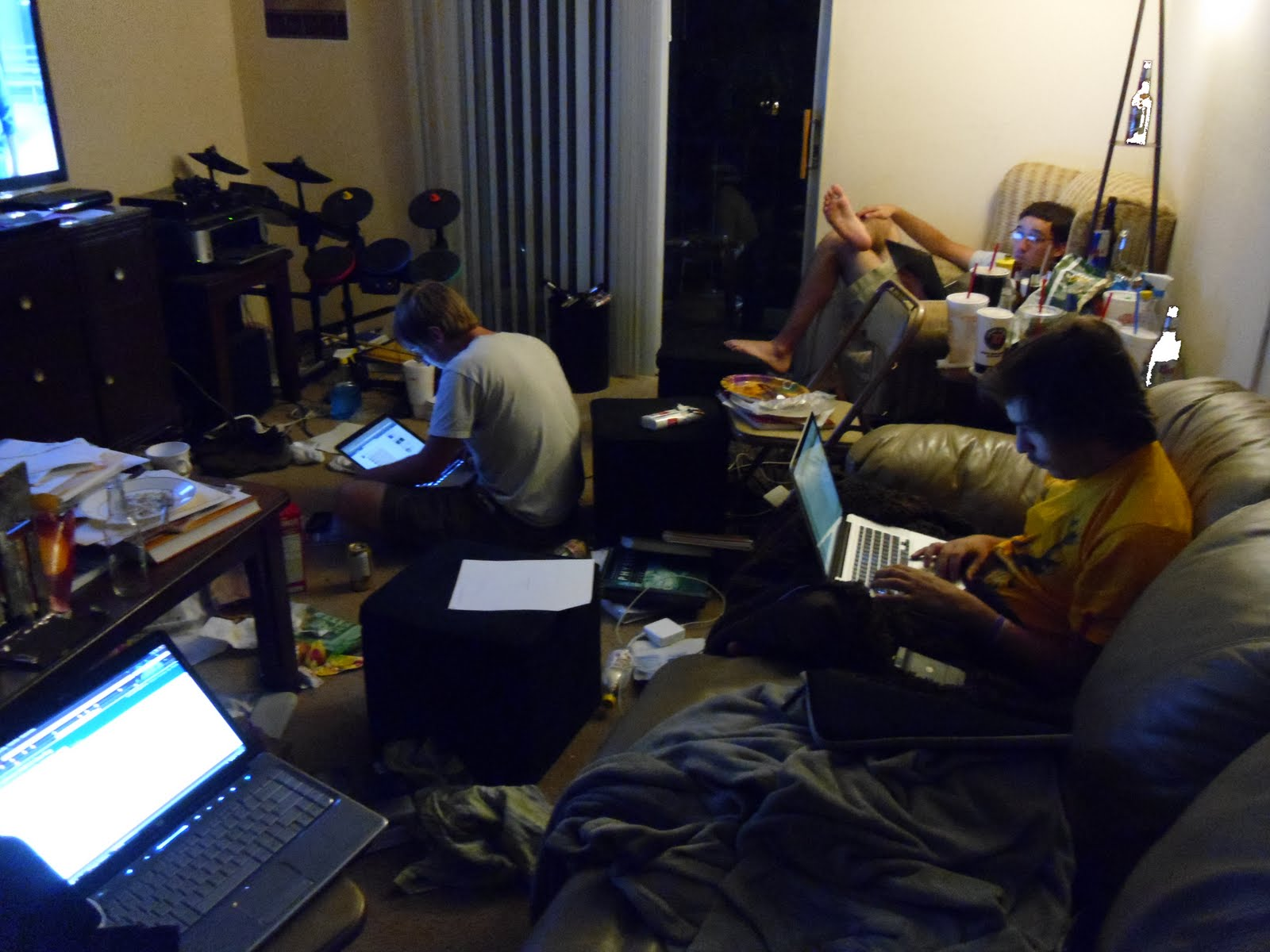 Three typical college students on their laptops in an extremely messy apartment.