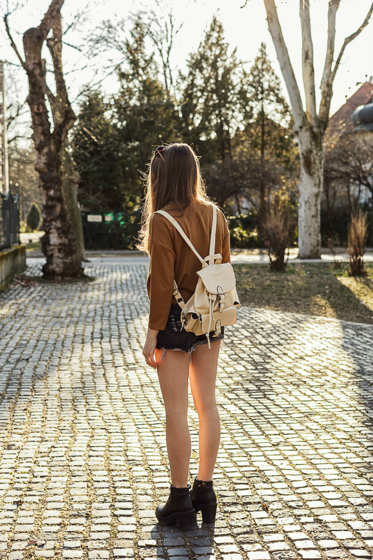 Emma, fashion blogger, wears cutoffs and a brown blouse