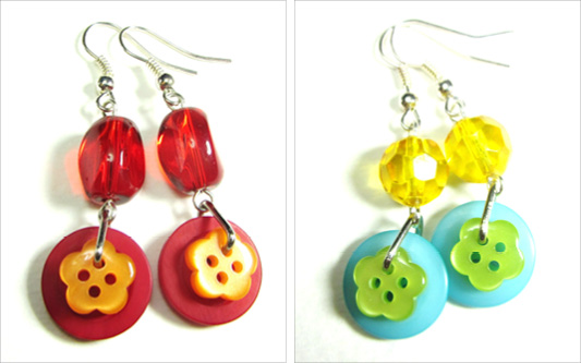 Long drop dangle earrings have colorful flower buttons hanging from large glass beads