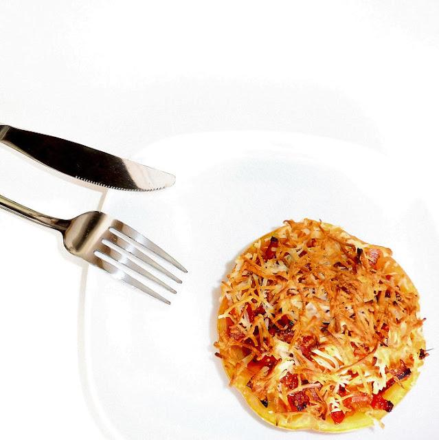Tomate relleno gratinado con cubiertos sobre un fondo blanco