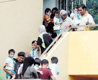 ANGGOTA polis membawa keluar murid-murid tadika selepas berakhir