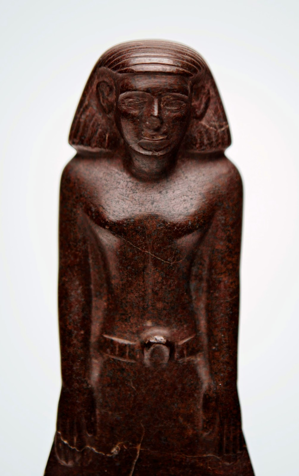 A close-up view of the torso and face of an Egyptian statue made in the likeness of a man.