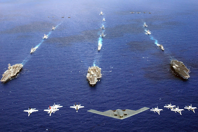 A B-2 Spirit and 16 other aircraft from the Air Force, Navy and Marine Corps fly over the USS Kitty Hawk, USS Ronald Reagan and USS Abraham Lincoln carrier strike groups